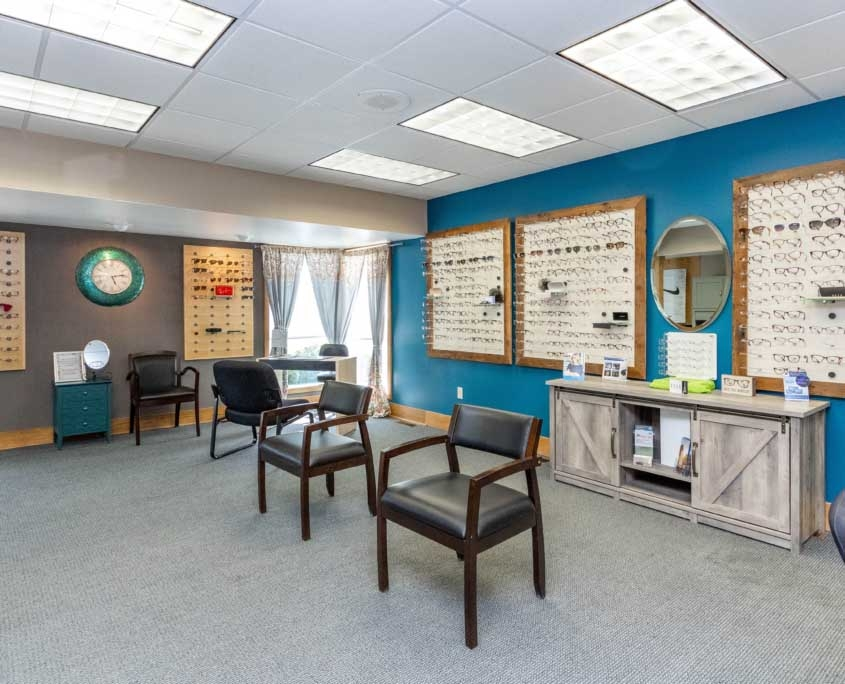 indoor view of advanced family eye care's independence location. there is prescription eyewear on the wall and waiting chairs in the center of the room