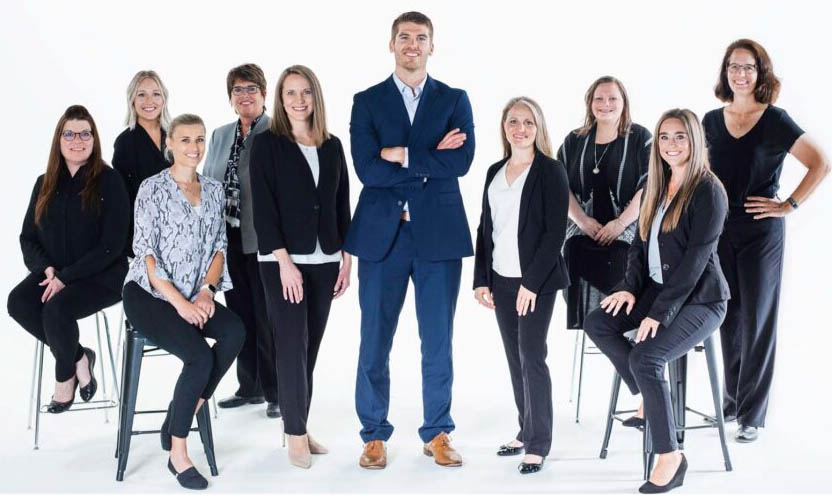 cedar valley eye doctor advanced family eye care employees posing for the camera. they are wearing business clothing and smiling with a white backdrop