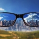 first person view staring through eye glasses at a cityscape. The image inside of the lenses is crystal clear, and the surrounding area is very blurry. This image illustrates myopia (nearsightedness), which is characterized by the inability to see clearly from a distance.